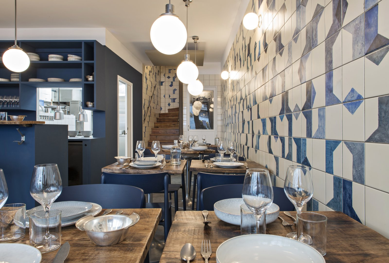 The hand-painted ceramic tile wraps along the wall and continues up the stairwell. Named after Belle Maison, after the owners' favorite beach, the restaurant is focused on seafood dishes.  Photo 5 of 6 in A Parisian Seafood Restaurant, Swimming in Shades of Blue