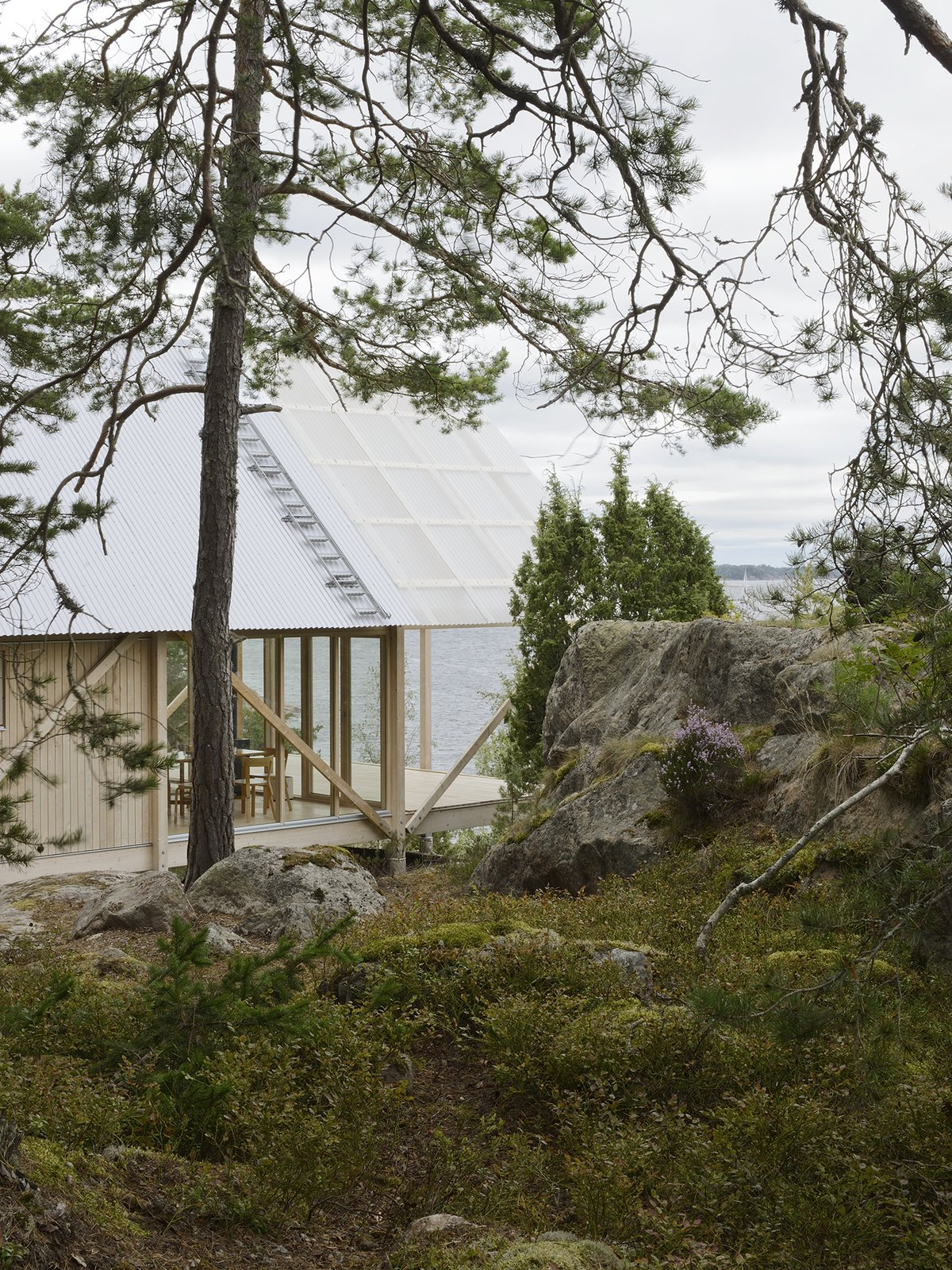 Exterior, House Building Type, and Wood Siding Material On Viggsö, an island of the Swedish Archipelago, architecture firm Arrhov Frick designed a two-story retreat, using simple but hardy materials. The roof, made from corrugated metal and fiber-reinforced plastic, joins the pine timber frame.  Photo 2 of 7 in A Swedish Summer Cabin That Sits  Above and Among the Trees