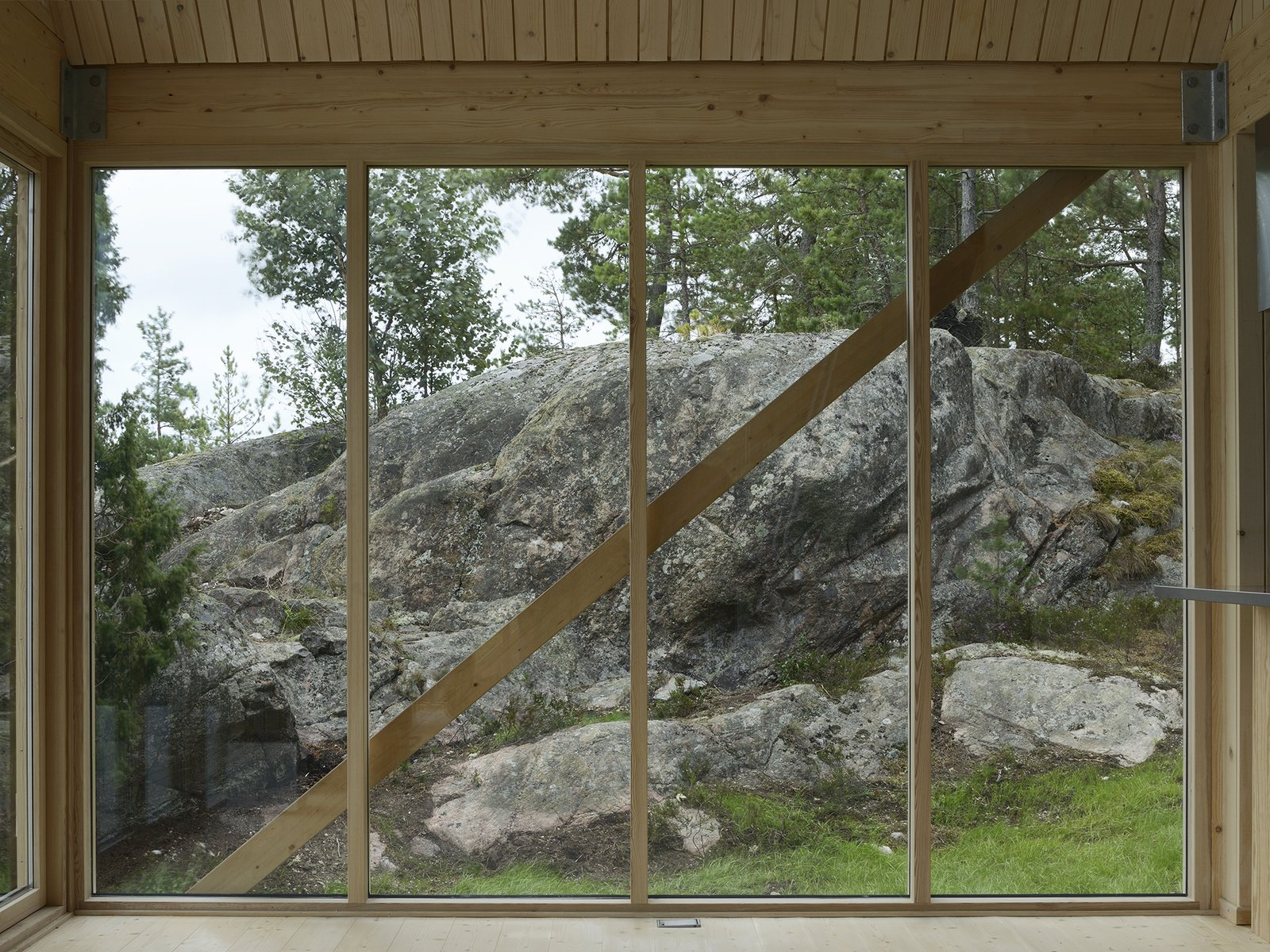 A simple timber frame and wide expanses of glass enhance the structure's connection to Viggsö's varied terrain, marked by rocky cliffs, wild-bent pine trees, heather, and lichen.  Photo 5 of 7 in A Swedish Summer Cabin That Sits  Above and Among the Trees