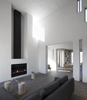Soaring ceilings and a fireplace mark the home's main living area.