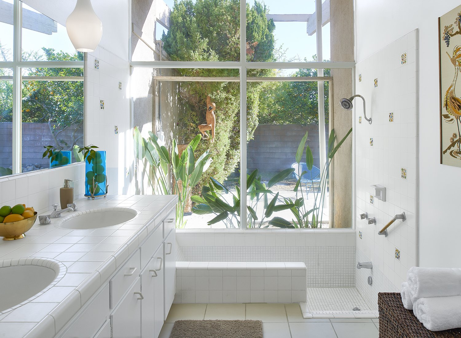 """The Jungle bathroom at the Monkey Tree hotel in Palm Springs. Accessories and art like the roadrunner needlepoint wall hanging were largely """"made by regular people and found in vintage stores,"""" Kathy says."""