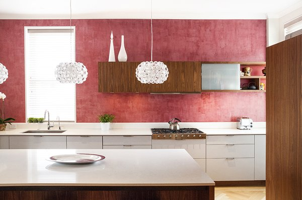 The kitchen's red Venetian plaster walls are a nod to a detail in the family's previous apartment. The walnut and lacquer kitchen system is by Henrybuilt.  Photo by Howie Guja Styling by Gorilla Styling  Photo 18 of 21 in Red, Red, and More Red! 20 Bold Interiors That Make a Statement