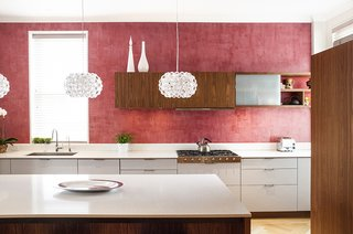 The kitchen's red Venetian plaster walls are a nod to a detail in the family's previous apartment. The walnut and lacquer kitchen system is by Henrybuilt.<br><br>Photo by Howie Guja<br>Styling by Gorilla Styling