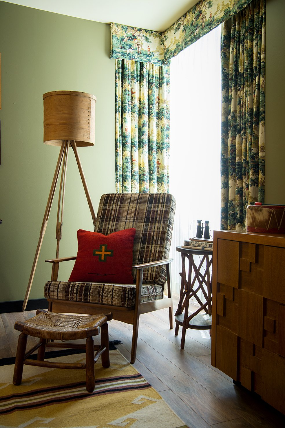 Bedroom, Lamps, Chair, Medium Hardwood Floor, Storage, and Rug Floor Hunting print draperies complement accessories and toys from the Camp Wandawega Land of Nod collaboration.  Photo 9 of 10 in This Wisconsin Hotel Suite Conjures the Best of Summer Camp—Hold the Bug Spray