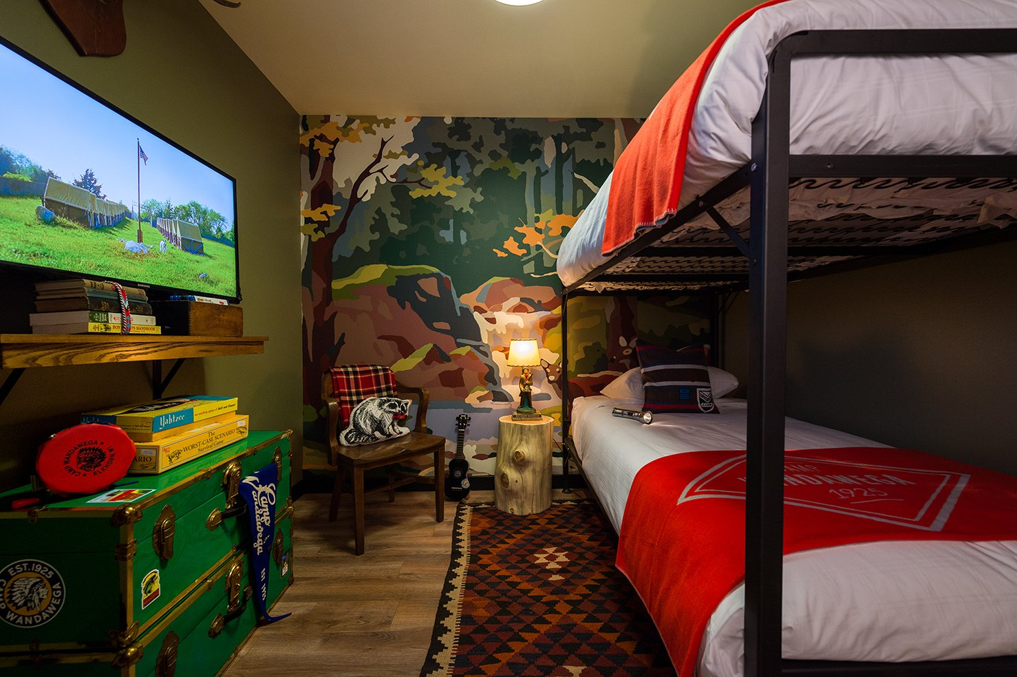 Bedroom, Bunks, Rug Floor, Medium Hardwood Floor, Night Stands, Lamps, and Shelves The media room features custom-designed bunks with Camp Wandawega for Land of Nod bedding.  Photo 2 of 10 in This Wisconsin Hotel Suite Conjures the Best of Summer Camp—Hold the Bug Spray