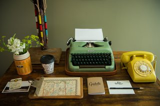 A working vintage typewriter and telephone top the antique desk.