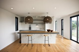 The kitchen island is made of concrete with an oak top and black steel edging—an industrial element within a project that celebrates nature.