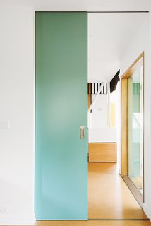 Sea green details appear throughout the house, peeking out from behind the exterior screen or on interior partitions.