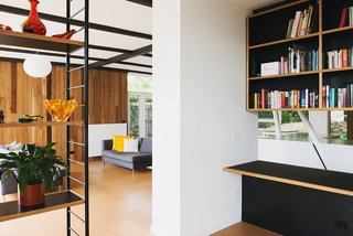 The built-in cabinetry reverses the home's usual organizational motif of a black grid against a timber frame.