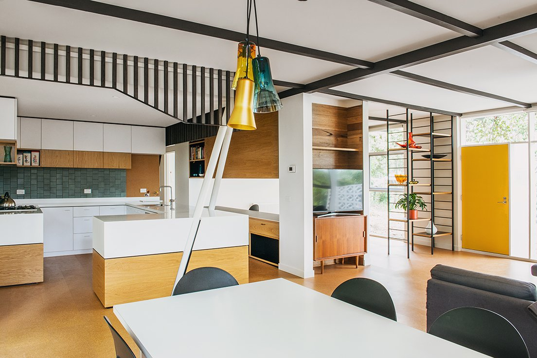 The black framework separating the kitchen and dining area was meant to echo the exterior cladding. Additional black details give the space a grounding geometry.  Photo 13 of 15 in An Australian Renovation Gives New Life to Midcentury Style