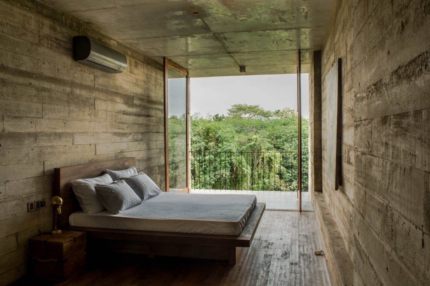 Bedroom, Bed, and Concrete Floor  Photo 1 of 7 in An Architect's Home and Studio Rises Above Rajagiriya