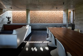 The primary living area opens to the main volume below it. The perforated brick walls aid with heat management.