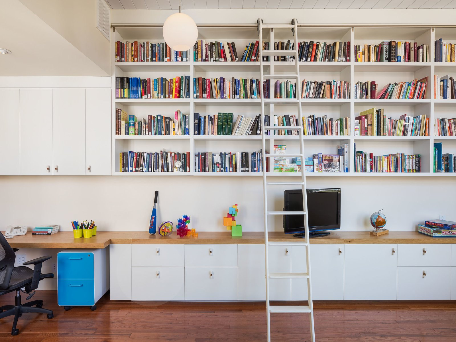 A ladder leads to built-in book shelves.