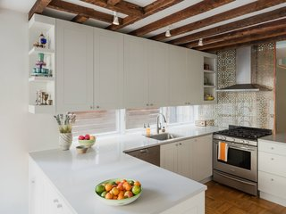 A bright new kitchen is the highlight of the renovation. The pattern behind the stove call to mind traditional Persian motifs. A row of windows provides a light-filled alternative to a backsplash behind the sink.