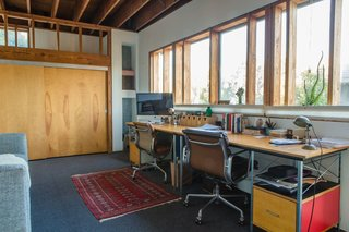 "Vintage Soft Pad chairs by Charles and Ray Eames for Herman Miller (an eBay find) and matching new Eames desk and storage units, also from Herman Miller, furnish a workspace on the mezzanine level. ""When we're both at home we speak to each other all the time,"" William says of the openness of the house."