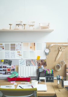 A shelf of models sits over a design station layered with inspiration.