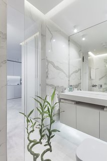 In the bathroom, marble walls provides a sleek backdrop.