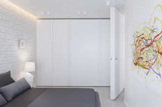 In the bedroom, storage was designed to fade away into the background, while a colorful painting pops against the white backdrop.