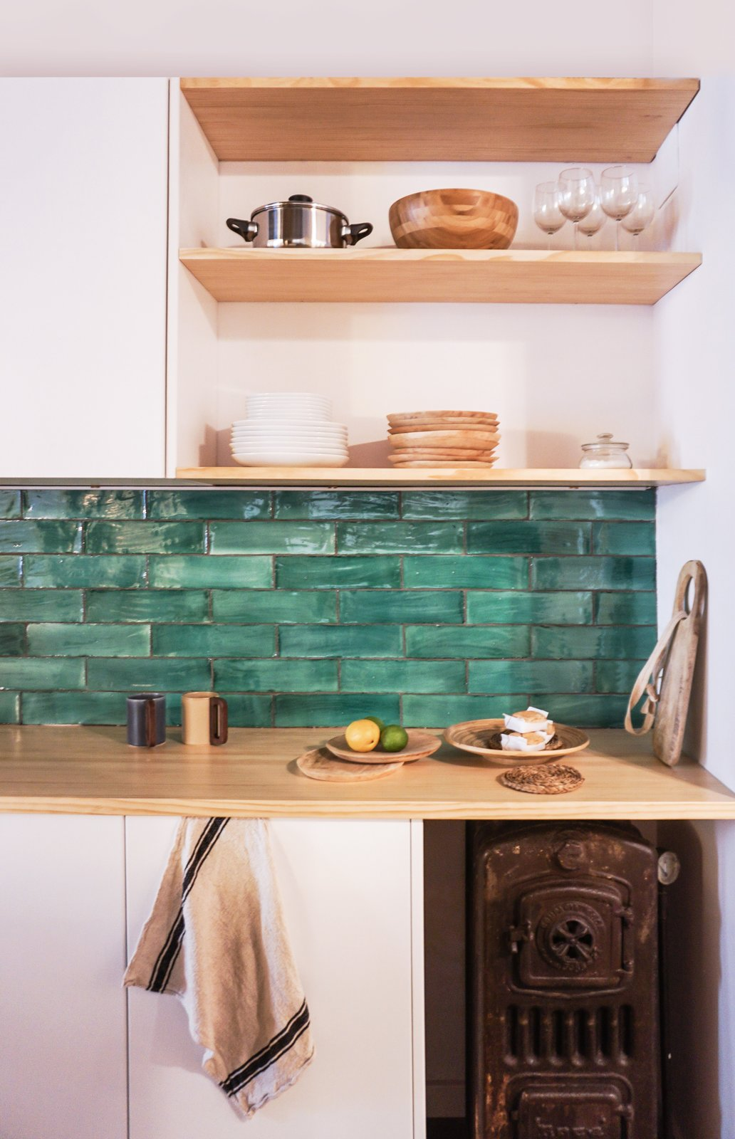 Kitchen, Wood Counter, and Ceramic Tile Backsplashe An original boiler the designers discovered during the renovation was kept in the kitchen as decoration. The counter is white pine, and the green tiles were sourced from Can Benito a studio in Mallorca.  Photo 3 of 9 in A Barcelona Apartment Gets a Softly Modern Renovation