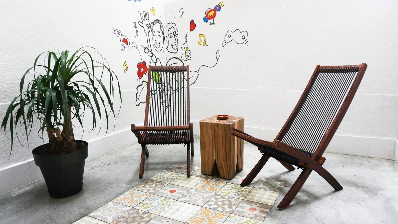 The patio features a cement floor inlaid with traditional <i>baldosa hidráulico</i> tiles by Pinar Miro. A friend of the resident painted the mural. Tagged: Living Room, End Tables, and Chair.  Photo 8 of 9 in A Barcelona Apartment Gets a Softly Modern Renovation