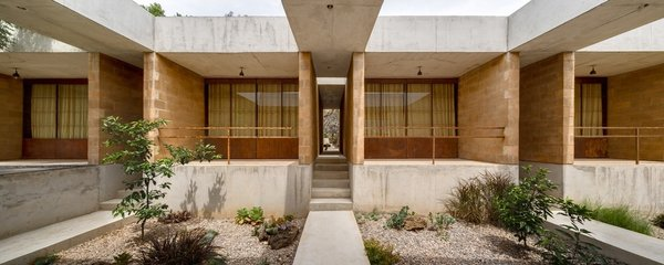 The materials—concrete, stone, and brick—reference the local architecture, tying the house to its site and making it easier to find a construction team.