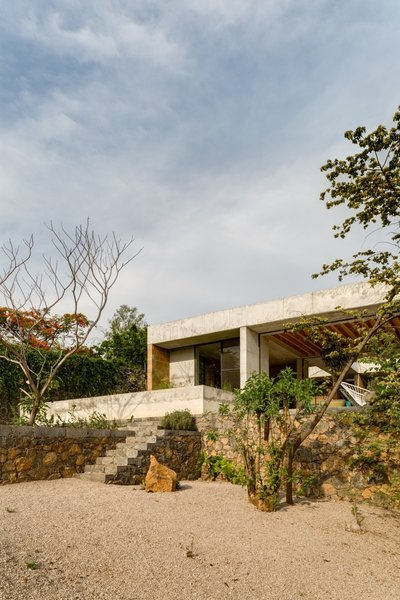 The concrete-and-brick house is perched on a stone wall.