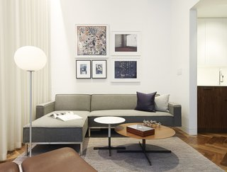 In Just 450 Square Feet, A New York Architect Crafts a Multifunctional Apartment of His Own - Photo 1 of 10 - The living room features a 12-foot-high ceiling, which drops to 8.5 feet in other areas of the apartment—an design feature architect and resident Christopher Kitterman used to organize the space. Behind the curtain, sliding glass doors open to a small terrace. The artwork includes a pair of Cindy Sherman prints, a framed Hermès scarf, and two of Kitterman's own photographs.