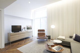 In Just 450 Square Feet, A New York Architect Crafts a Multifunctional Apartment of His Own - Photo 3 of 10 - The living room furniture sticks to a soothing palette. The sectional is by Gus, the brown leather Spring chair is by Erwan Bouroullec for Cappellini, the silver side table is from Design Within Reach, the Glo Ball floor lamp is by Jasper Morrison for Flos, and the Bob tables are by Jean-Marie Massaud for Poltrona Frau. A photograph by the architect rests on a credenza from ABC Home, the same source for the rug.