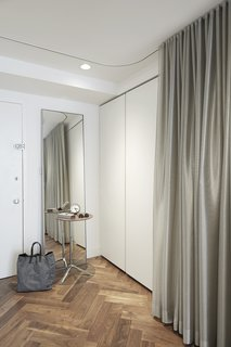 By the entrance, a silver curtains in KnollTextiles fabric hide a Poliform storage system and a Murphy bed.