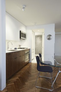 In Just 450 Square Feet, A New York Architect Crafts a Multifunctional Apartment of His Own - Photo 9 of 10 - The galley kitchen features a slim Corian countertop and backsplash over rich walnut cabinetry. In the pantry and bathroom areas beyond, white terrazzo flooring replaces wood. The wall at the back of the shower is clad in large-format Blue de Savoie stone tiles.