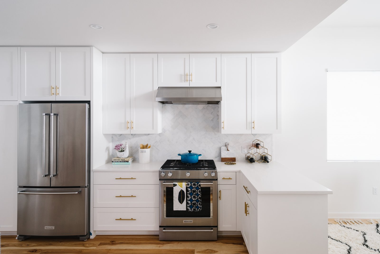The bright white kitchen is accented with metallic door pulls and a marble tile backsplash.  Photo 7 of 7 in Sustainability is the Centerpiece of This New Austin Development