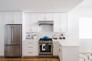 The bright white kitchen is accented with metallic door pulls and a marble tile backsplash.