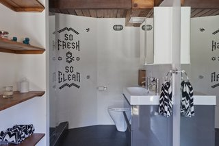"Chad looked to his experience in graphic design when creating his family's home. Elements of text and graphics can be found throughout, including the inlaid tiles that spell out ""So Fresh & So Clean"" in the guesthouse bathroom."