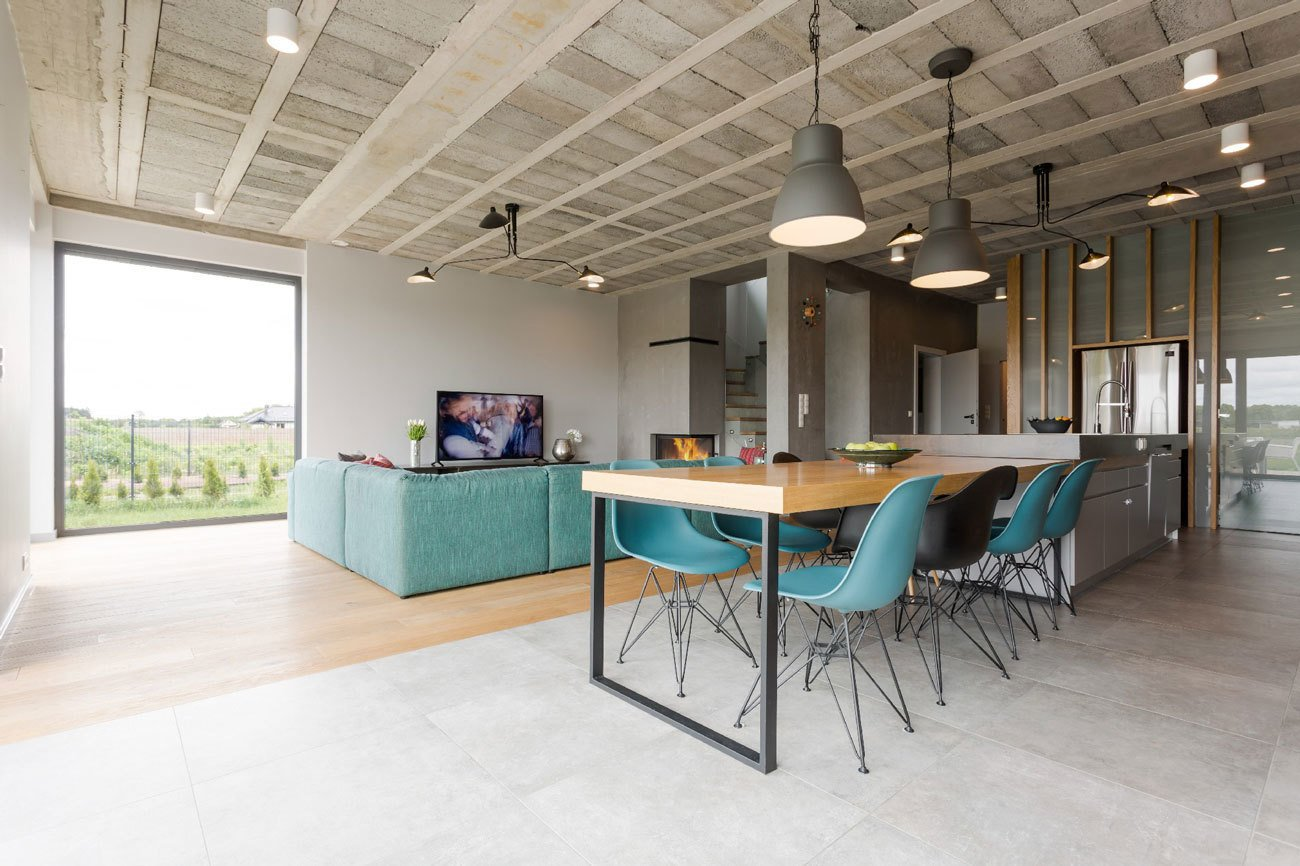 A mix of DSW and DSRA Eames Plastic Side Chairs from Vitra are seated at the dining table, which extends from a stainless steel countertop. Tagged: Dining Room, Table, Chair, Pendant Lighting, and Light Hardwood Floor.  Photo 2 of 4 in Rarely Do Family Homes  Look So Raw