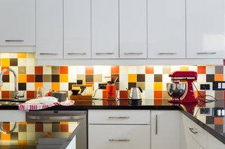 "The backsplash is an exuberant mix of colorful tile. ""We used a randomizer algorithm to design the multi-colored non-pattern,"" says Lori."