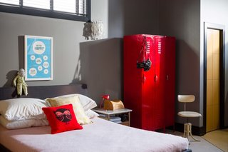 A red gym locker, repurposed as storage, is a whimsical touch in the bedroom.