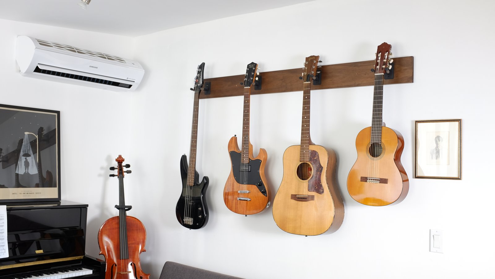 Living Room Composer and podcaster Hrishikesh Hirway hangs guitars and a bass from wall-mounts in his Echo Park home to conserve space.  Photo 1 of 7 in The L.A. Home of Song Exploder's Hrishikesh Hirway Is Barely Larger  Than a Music Box