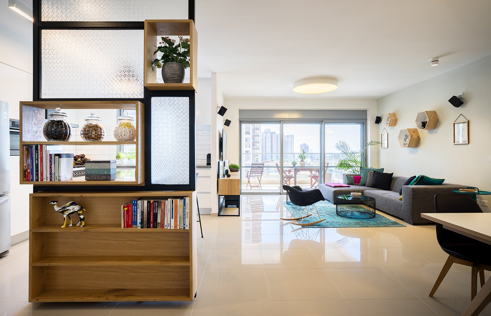 The most immediately striking feature of this 1,400-square-foot in a 21-floor high-rise is the shelving unit/room divider between the kitchen and living area.  Photo 2 of 4 in A Riotous Makeover for a Generic  High-Rise Home