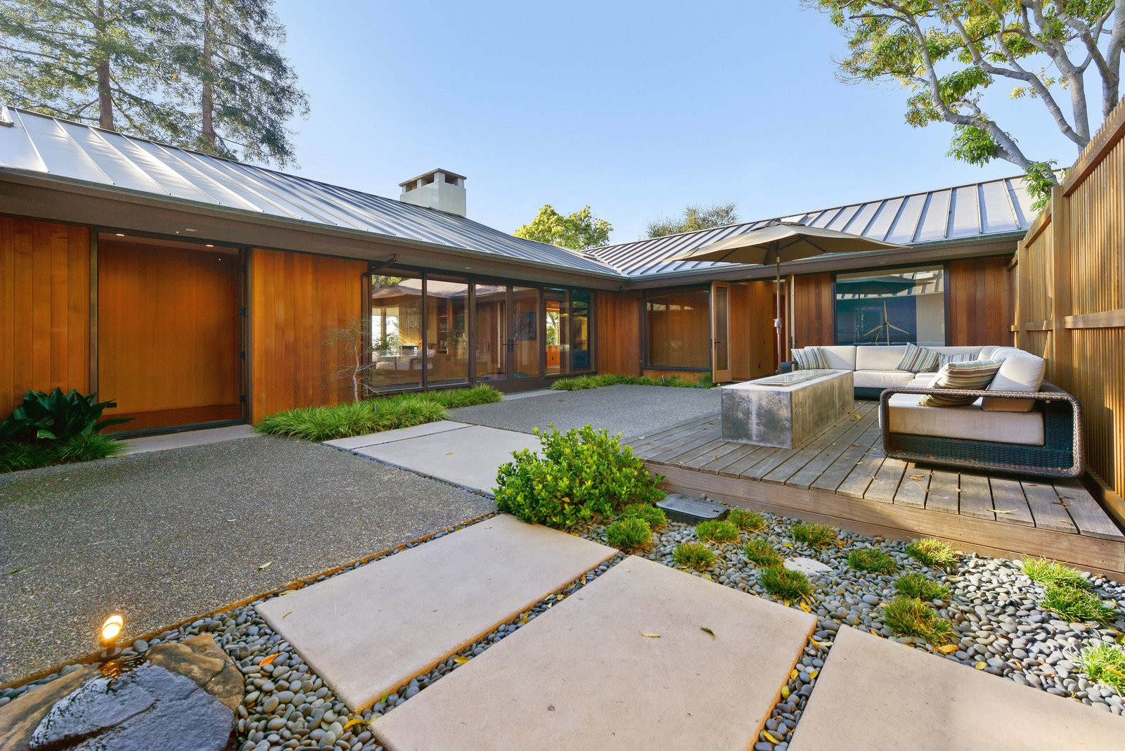 Shannon Bloemker's hillside home in Piedmont, California, is arranged in a C-shape with protected courtyards.  Photo 2 of 6 in A Quintessential Midcentury Home Goes LEED Platinum