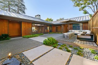 A Quintessential Midcentury Home Goes LEED Platinum - Photo 1 of 5 - Shannon Bloemker's hillside home in Piedmont, California, is arranged in a C-shape with a protected courtyard landscaped by Gardener's Guild. The fire pit is by Spark Linear Burner.
