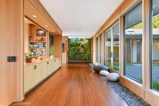 A Quintessential Midcentury Home Goes LEED Platinum - Photo 2 of 5 - The Mexican river rocks that hardscape the outdoors continue in the interior hallway, which connects the bedroom and living spaces. The green wall system is by Woolly Pocket. The flooring is Ecotimber strand-woven bamboo.
