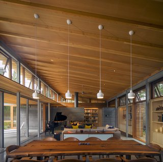 Honest materials appear throughout this Los Altos, California, home. In the double-height living area, Mantis chairs by BassamFellows surround a custom live-edge dining table, fashioned from an old Claro walnut tree with help from Menlo Hardwoods.