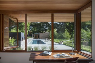 Looking out from one of the home offices, a board-formed concrete garden wall and linear pool draw the eye toward a guesthouse.