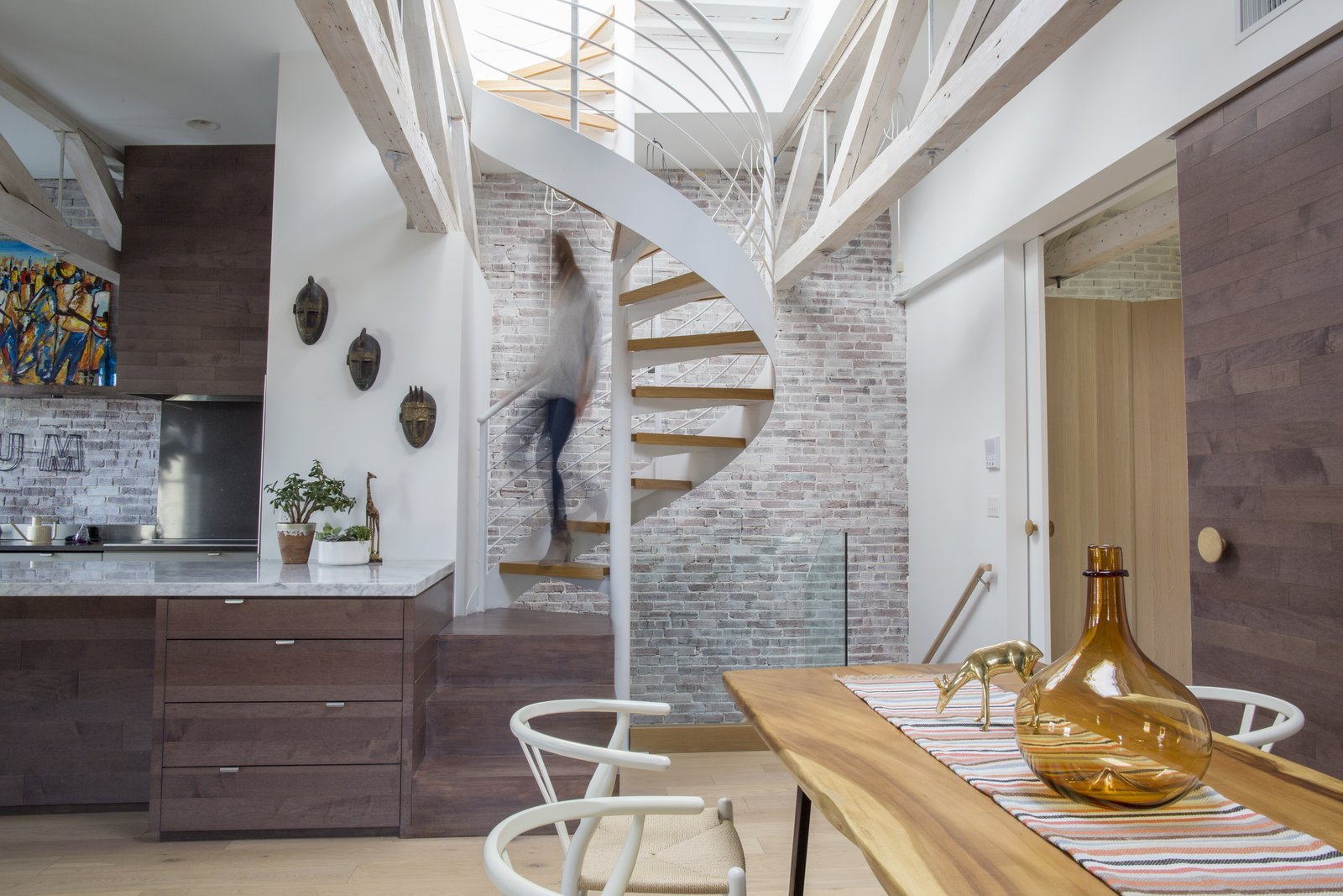 Staircase, Metal Railing, and Wood Tread When Alan Ricks and Cristina de la Cierva moved into their Boston condo, a ship's ladder was taking up space in the main living area. Following a lengthy renovation, a spiral staircase provides rooftop access.  Photo 2 of 5 in This Modern Boston Renovation Expertly Mixes in Colorful Craft Finds