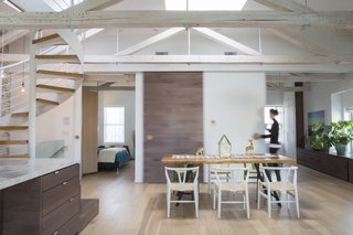 Natural light entered the original apartment through three sides plus a skylight. A wall that blocked the passage of light between the bedroom and main living area was replaced with a custom 10-foot-long barn door, which is outfitted with coat hooks from Design Within Reach that the residents use as pulls. The dining table is from Mohr McPherson.