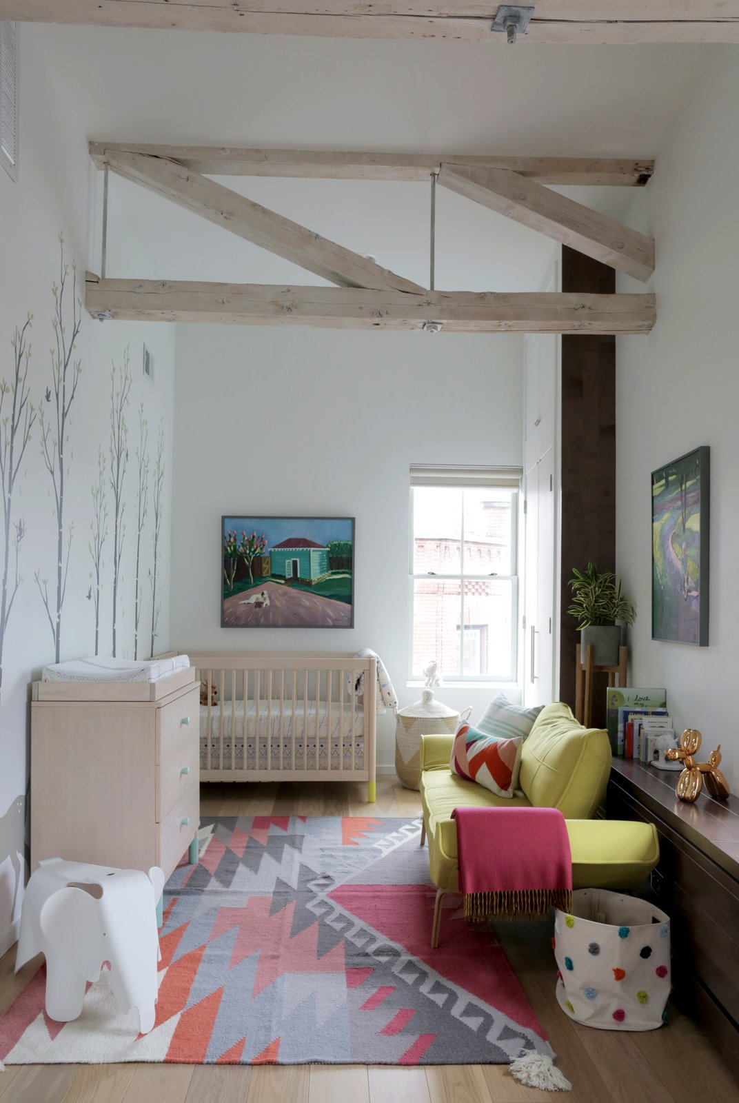 Kids Room, Bedroom Room Type, and Light Hardwood Floor For the couple, who are expecting, adding a nursery was a key component of the renovation. The home's historic trusses were lightly sanded and whitewashed.  Photo 5 of 5 in This Modern Boston Renovation Expertly Mixes in Colorful Craft Finds