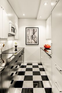 The 650-square-foot apartment has a galley kitchen with checkered black-and-white tile.