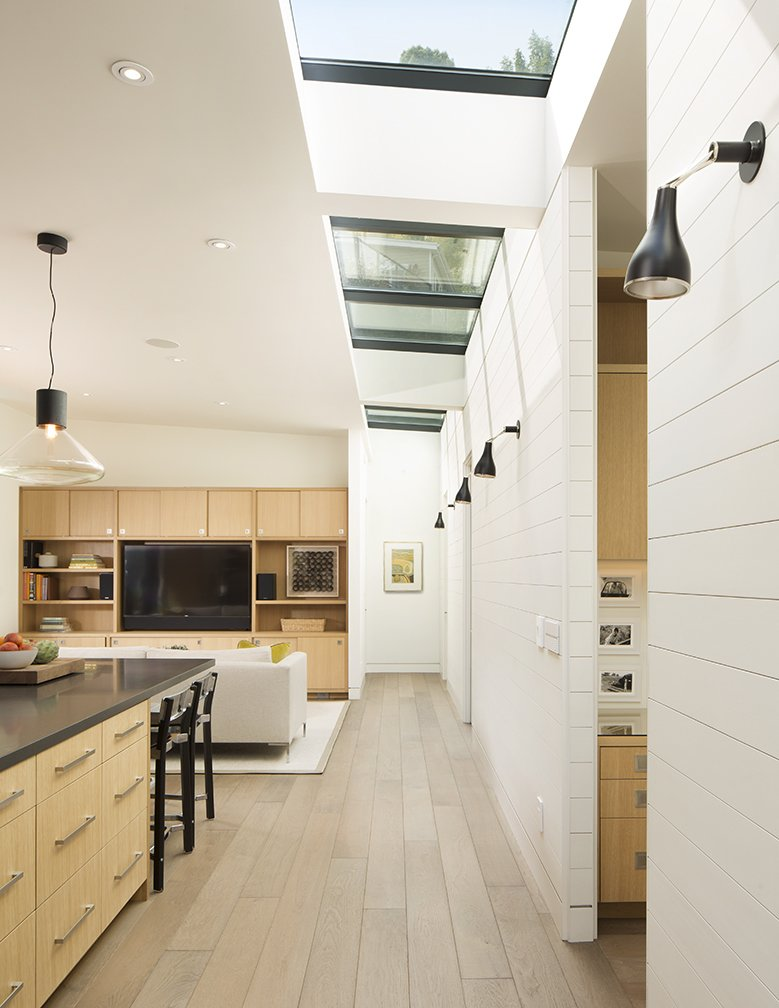 A painted wood wall marks the boundary between the home's public and private wings. Linear skylights bathe the open-plan communal area in light.  Photo 4 of 5 in A New Spin on the Suburbs in Marin