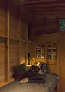 Opposite Jim's workstation, the modest interior accommodates a single bunk outfitted with Woolrich linens and pillows designed by Jim's wife, Beth Wheeler.