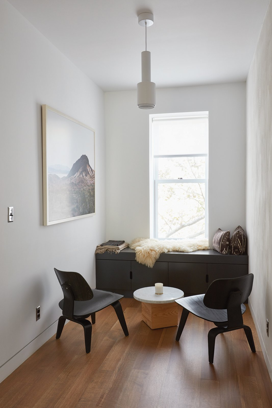 "Living Room, Chair, Storage, Pendant Lighting, and Medium Hardwood Floor ""In an eighteen-foot-wide brownstone, there's only so much you can do. But we wanted  it to feel fresh,"" Keith Burns, architect and resident  Photo 9 of 16 in Forever Changes"
